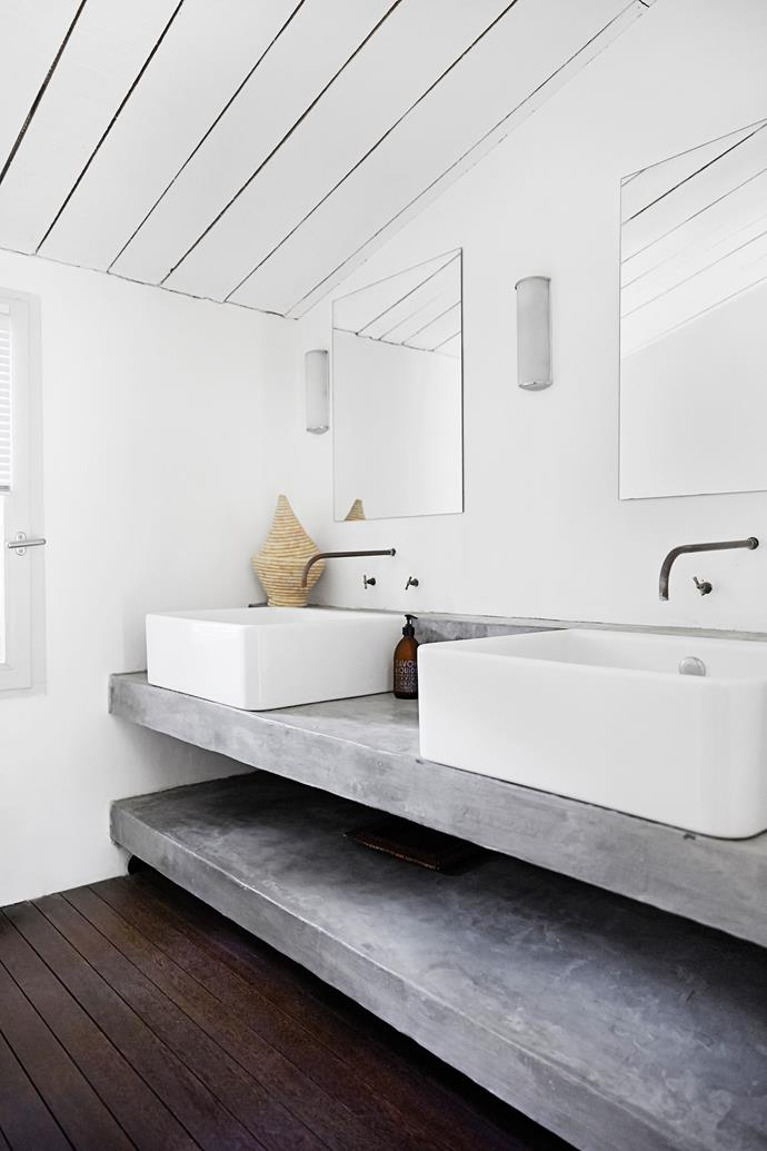 The bathroom is sublimely simple, with two white porcelain washbasins on the floating concrete vanity.The dark timber floor grounds the space with its earthiness.