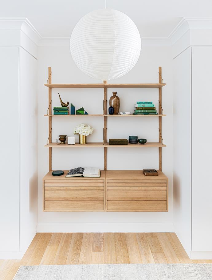 An 'Akari' pendant light from [Space](http://www.spacefurniture.com.au/) hangs in the entry above the 'Royal System' shelving from [Great Dane](https://greatdanefurniture.com/).