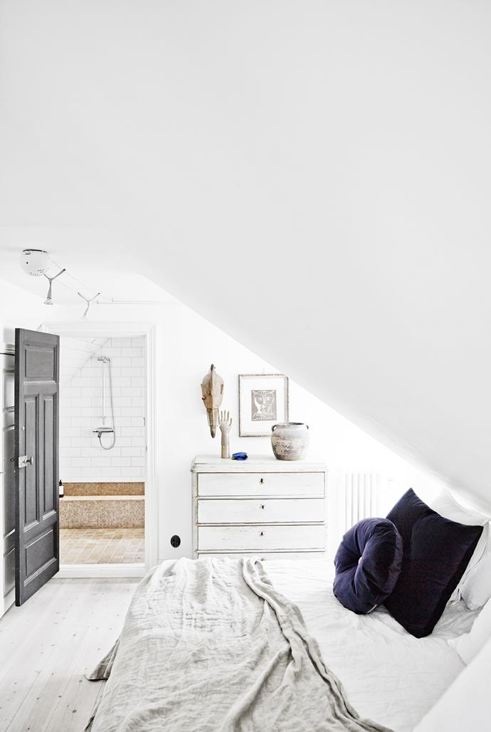 Track lighting and loosely draped linen keep the bedroom casual. Its roughly finished chest and artefacts reference the ensuite inspired by ancient roman baths.