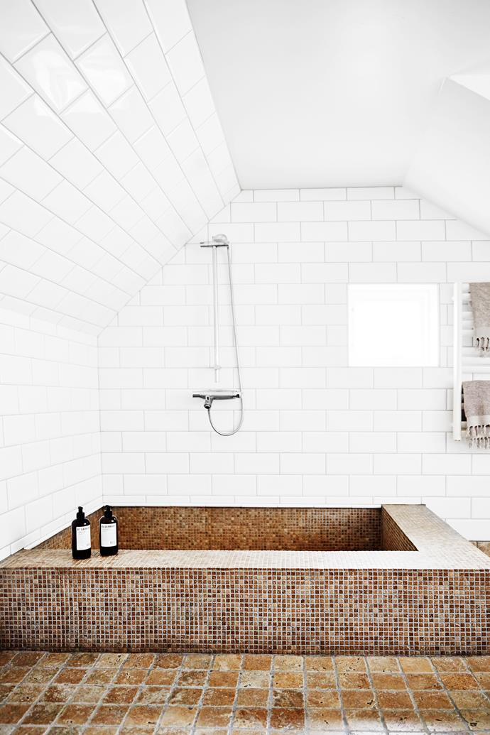 The couple designed their own tub using natural stone and white tiles.
