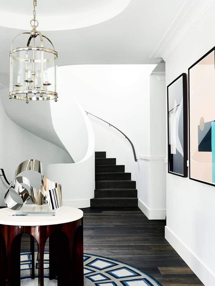 A sinuous, ribbon-like circular staircase connects the three floors of the home.