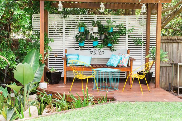 This vertical garden from Freedom is a fun way to liven up a fence, while the bright pillows and table from Kmart add a pop of colour.
