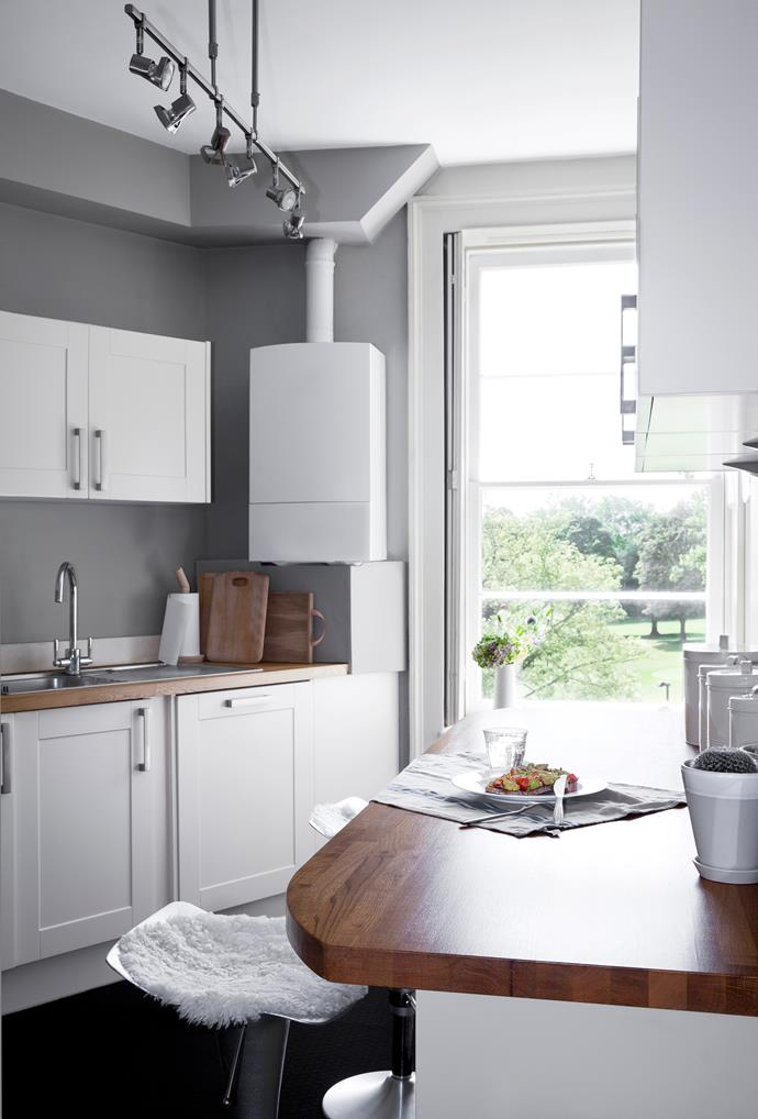 The kitchen continues the neutral scheme with mid-grey walls, white Shaker-style cabinetry and timber benchtops. Even the benchtop accessories are white or timber!