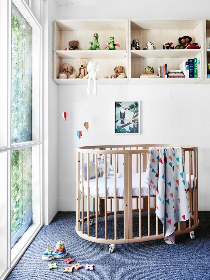 """Henry's room, at the rear of the house, features a floor-to-ceiling window that is externally shaded by a curtain of ivy. Cot from [Stokke](https://www.stokke.com/en-au/home). Custom-designed shelves by [Foomann Architects](http://www.foomann.com.au./ 