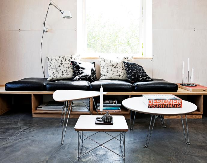 Black leather cushions transform this custom-made sofa into a comfortable seat while compartments below provide storage for magazines and books.