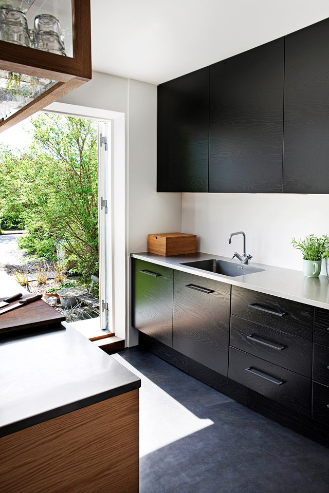 "Cleverly designed, this black kitchen features [custom storage](https://www.homestolove.com.au/7-custom-storage-solutions-that-look-amazing-4708|target=""_blank""), with a fridge tucked away beneath the centre island. *Photo: Morten Holtum / Living Inside*"