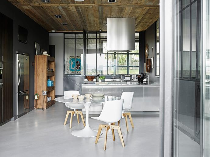 A glass and metal wall separates the kitchen from the living room. The cooktop and sink are situated on the stainless-steel island bench.