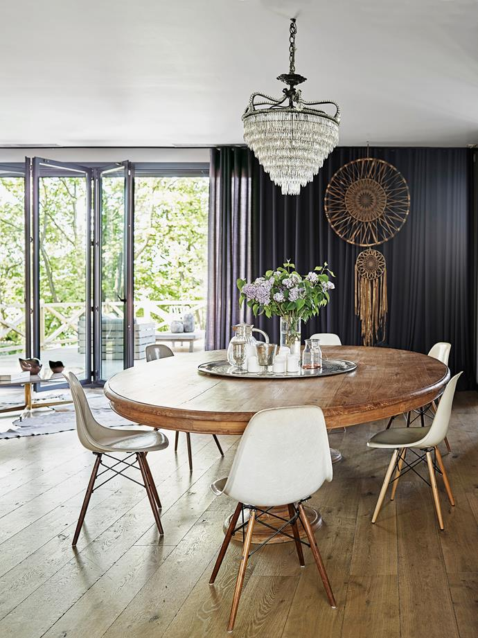 A 19th-century oak table and chandelier are juxtaposed with a handcrafted dream catcher, from a market.