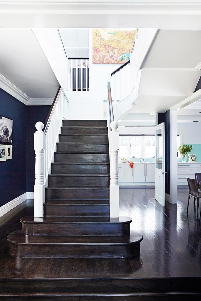 By removing three walls, Anna Maria ensured the home's spaces flow without interruption. The walls are painted in cocooning indigo, which frames a cluster of family photos. Artwork on stairwell by Angelina George.