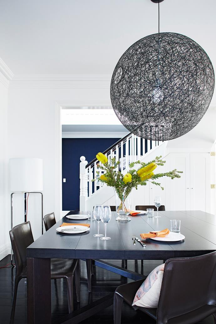 The dark dining setting brings gravitas to the white interior.