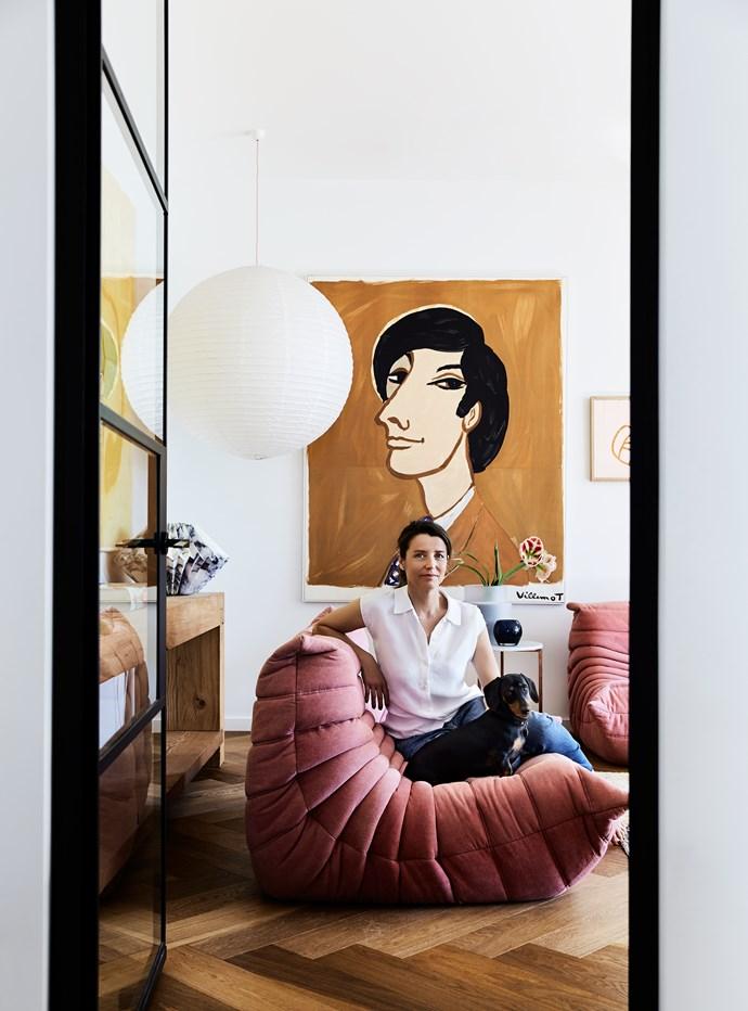 """Rachel cuddles up with Sydney Sausage on her [Ligne Roset](https://www.ligne-roset.com/au/) """"Togo"""" sofa. A large paper shade lights up an original Bernard Villemot portrait from [Vintage Posters Only](https://www.vintagepostersonly.com/)."""