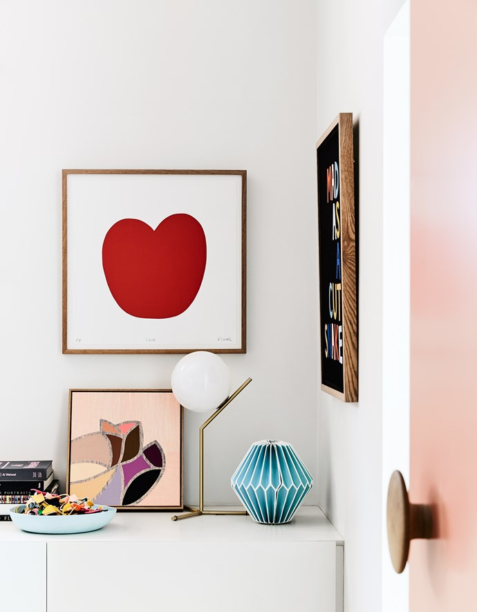 """Rachel's paintings and prints hang in her home office as well as a """"Mad as a cut snake"""" tea towel and paper sculpture by Castle."""