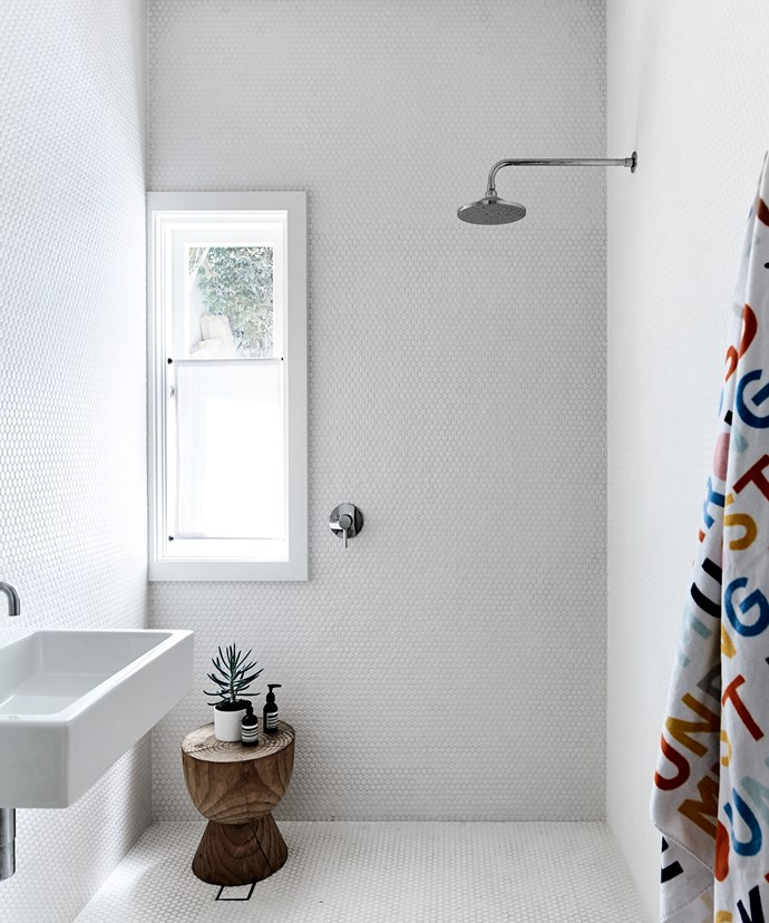 """Floor-to-ceiling tiling in the bathroom is simple yet effective. """"It has a little bit of detail that says everything and nothing all at the same time,"""" Rachel says."""