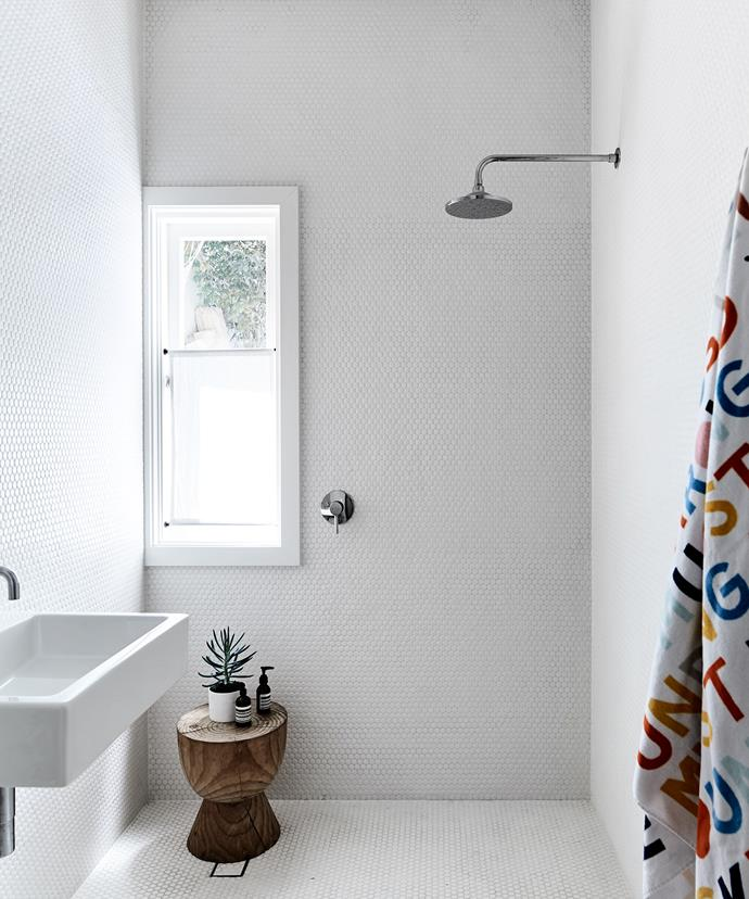 "Floor-to-ceiling tiling in the bathroom is simple yet effective. ""It has a little bit of detail that says everything and nothing all at the same time,"" Rachel says."