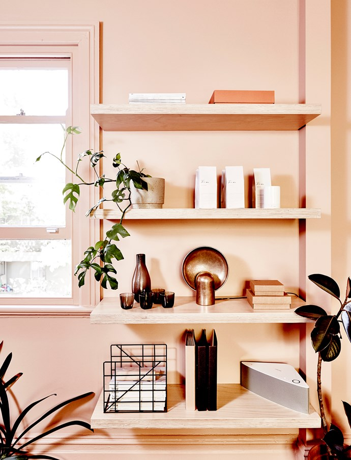 """Open shelving displays a Henry Wilson """"Surface Sconce"""", a HAY jug and glasses, Triibe candles, a Ferm Living magazine rack and plants from the Plantarum."""
