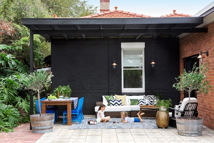 """""""My interior designer friend, Melissa Shepherd, encouraged me to paint the entire back wall of the house black. We left one wall raw brick, added the pergola and installed the copper lights,"""" says Elaine."""