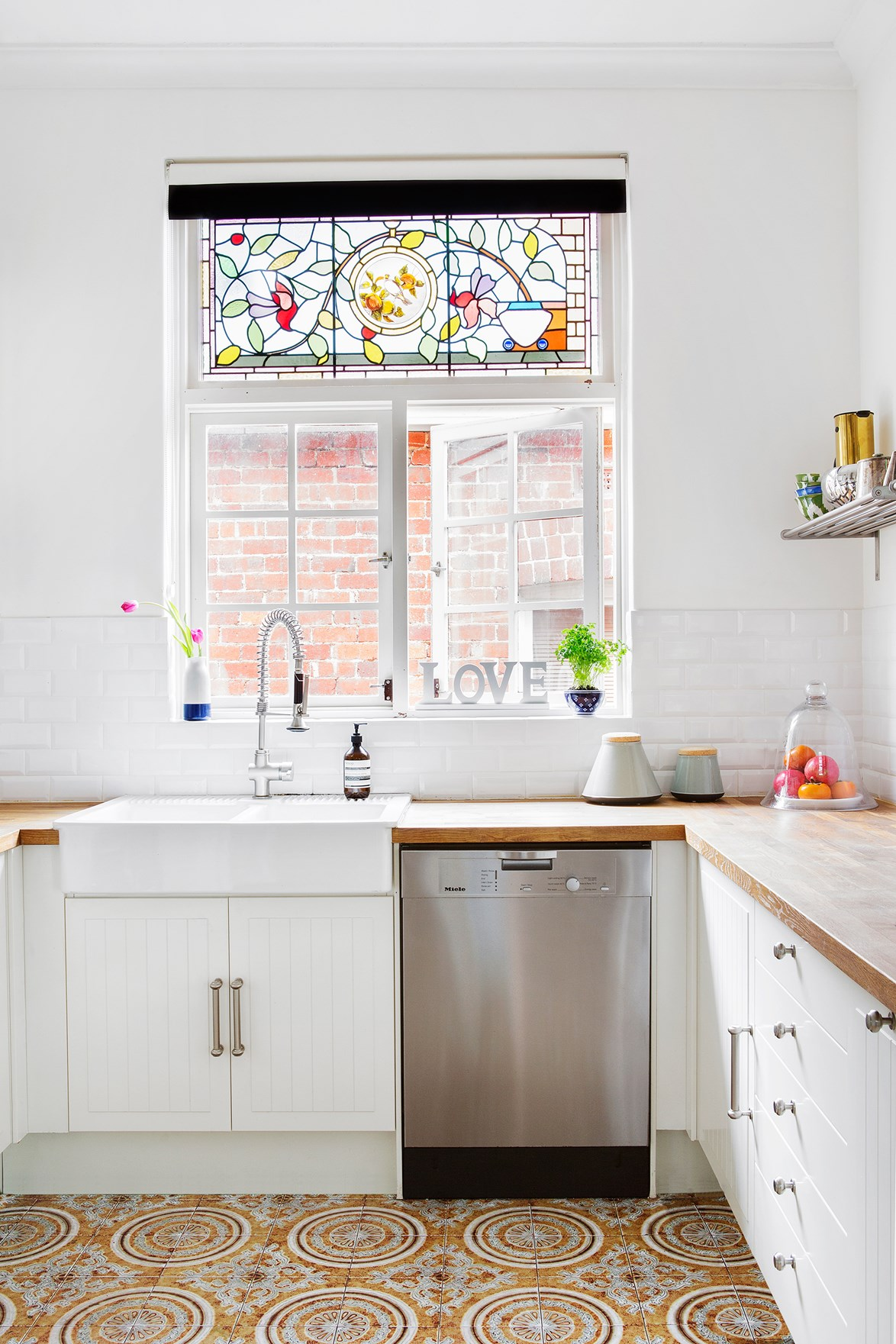 "This [Perth kitchen](https://www.homestolove.com.au/hollywood-style-californian-bungalow-in-perth-4750|target=""_blank"") was renovated using IKEA flat-pack cabinets in a beadboard style. The beadboard cabinets complement the home's period details, stained-glass windows and timber benchtops."