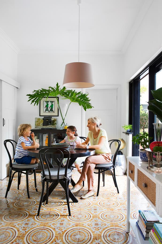 White walls in the kitchen/dining area are contrasted with more black detailing in the form of window frames, the dining table and classic bentwood chairs with ticking stripe seat pads.