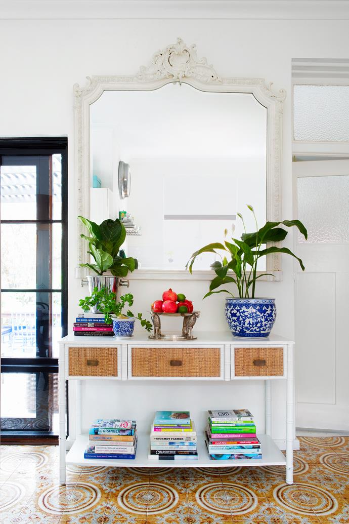 """In the kitchen, the """"wacky"""" original floor tiles have been made into a feature. A white rattan console and oversized mirror add a touch of Caribbean style."""