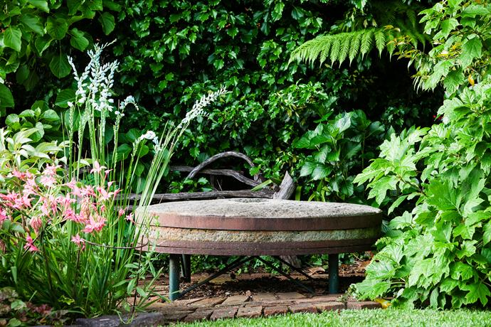 An old millstone from the historical Crown Mill has been upcycled into a garden table. Ivy covers the carport behind, while gladioli, Ixia viridiflora and Hydrangea quercifola 'Snow Flake' offer coloured blooms in turn.