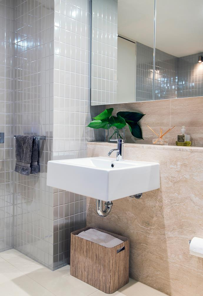 Soothing travertine tiles on the vanity are balanced by the sparkling glazed tiles and mirror.