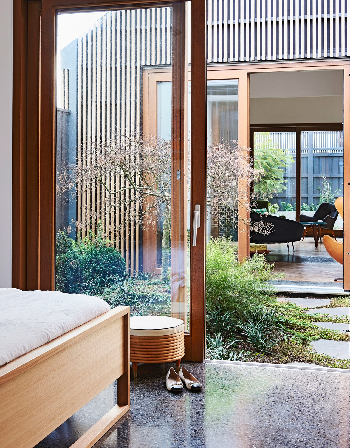 "When a pair of [mid-century modern design enthusiasts built their home](https://www.homestolove.com.au/melbourne-house-by-steffen-welsch-architects-4783|target=""_blank""), a set of internal courtyards were an absolute *must*. ""I love having a garden to tinker with and the freedom the pets have,"" says the owner. *Photography: Eve Wilson / Styling: Heather Nette King / Story: Australian House & Garden*"