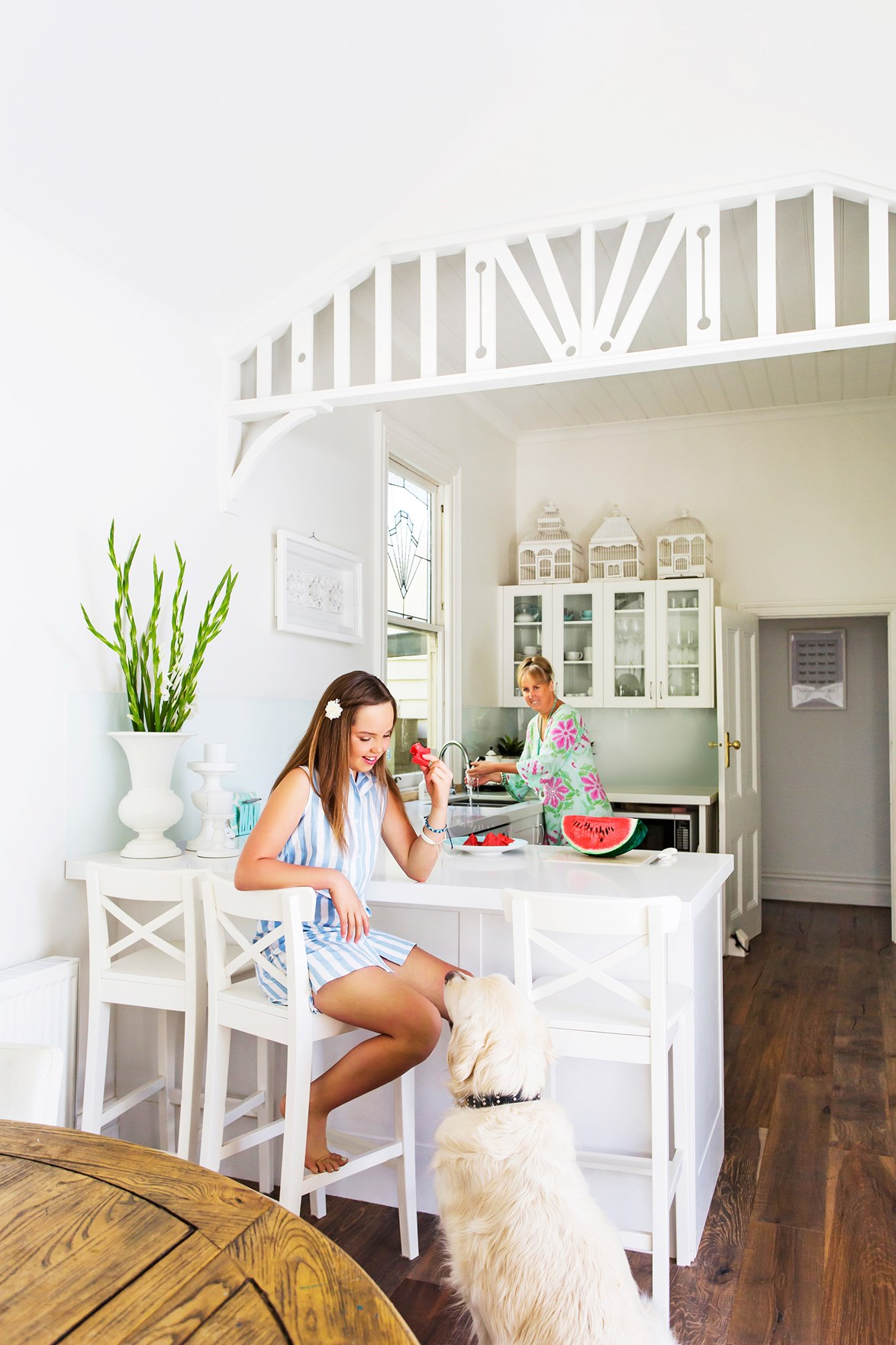 A crisp white palette combined with classic panelling and fretwork gives this cottage kitchen a Hamptons vibe. Photo: Katherine Jamison / *homes+*