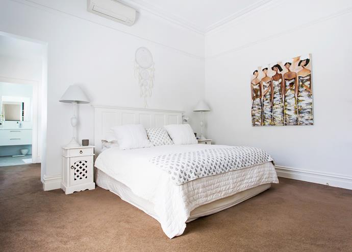 A soothing all-white palette in the master bed puts the artwork, bought on holiday in Bali, in the spotlight.