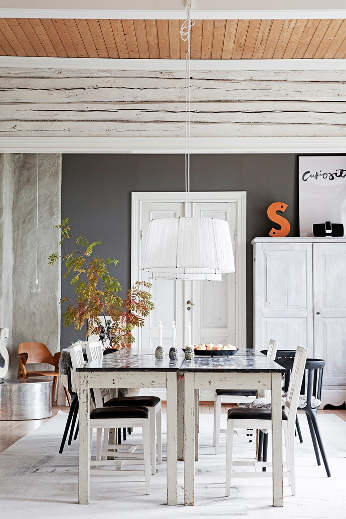 Old craft tables pushed together make one larger dining table. Generous doses of timber add texture and warmth to the monochrome palette while a dark grey wall and concrete chimney give the room more depth.