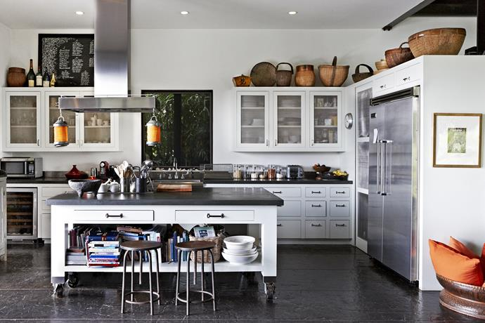 """The kitchen, with its classic [Shaker-style](http://www.homestolove.com.au/simple-spaces-inspired-by-shaker-style-1847 target=""""_blank"""") cabinetry, is tucked into a corner behind the dining zone. Stone benchtops echo the floor and give a sense of balance to the room."""