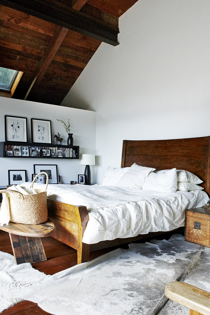 The master bedroom, with its comfy old sleigh bed, is tucked into the home's loft next to a balcony that overlooks the pool.
