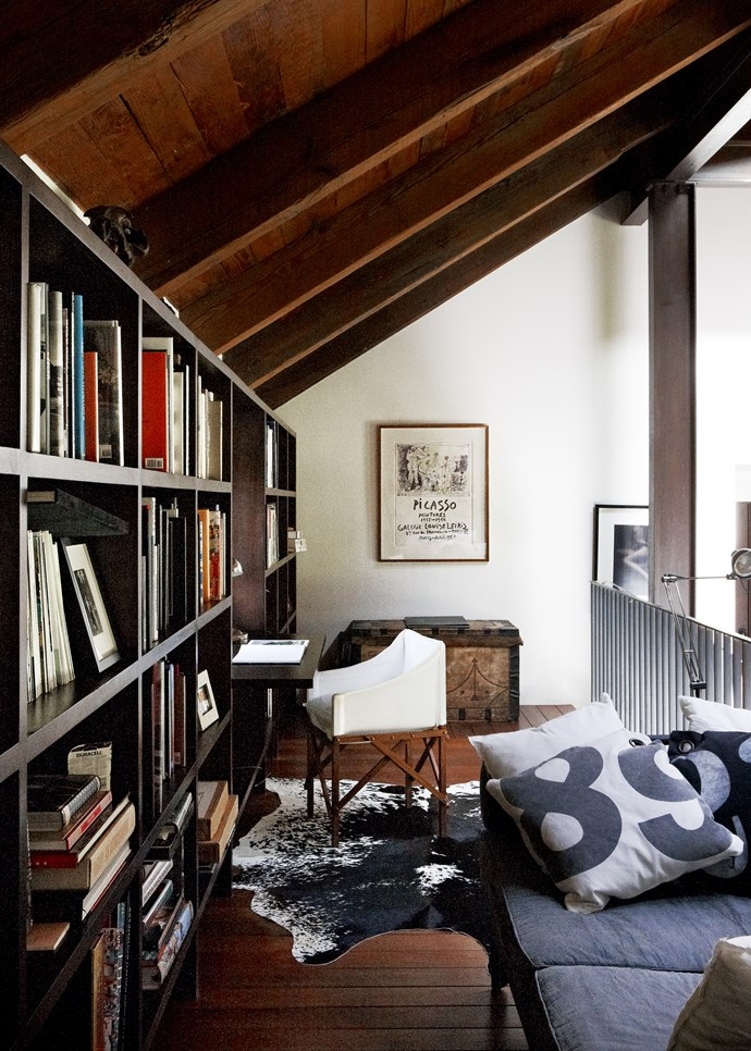 In the library, russet wood tones in flooring and vaulted wooden ceiling are the essence of country style in an urban setting. The mix of vintage and modern pieces is just right.