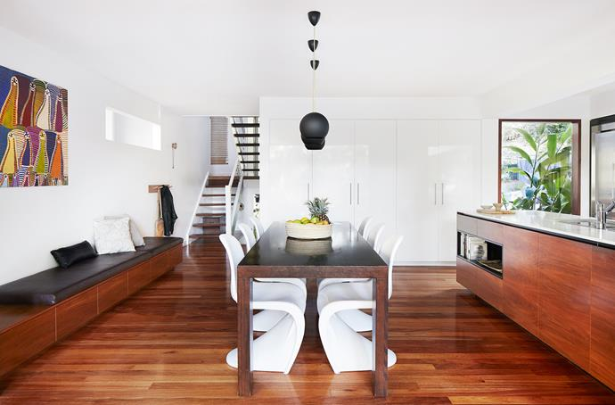 White-gloss finishes balance rich timber surfaces in this shared open-plan space. Custom dining table and bench seat by Blok Furniture.
