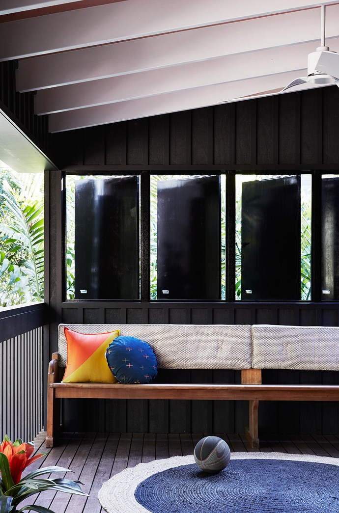 Adjustable Japanese-inspired shutters block harsh western sun and allow the family to make full use of this airy space. Vintage pew with custom back cushion in fabric from Walter G.