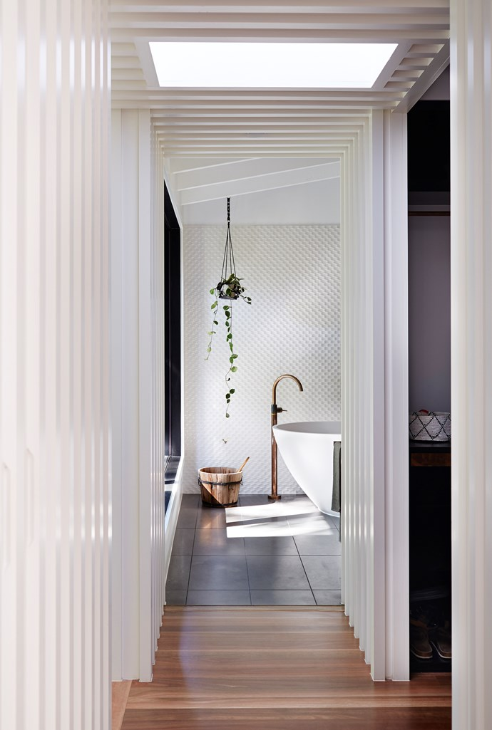 Elements in this well-composed master ensuite range from honed bluestone and distressed metal to textural ceramics and living greenery.