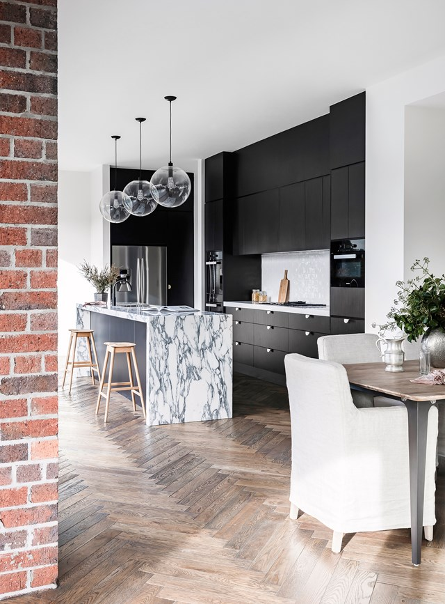 "The low-sheen black cabinetry used in this kitchen in a [contemporary new build](https://www.homestolove.com.au/contemporary-new-build-brisbane-by-sutcom-constructions-4857|target=""_blank"") in Brisbane is brought to life with a striking black and white marble island bench. *Photo: Maree Homer / Story: Australian House & Garden*"