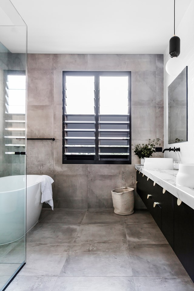 "On one hand, large-format concrete-look wall and floor tiles cater to this ensuite bathroom's industrial look; while on the other, a marble benchtop creates a sense of luxe. The owners describe their home as ""grand and luxurious, but not at all pretentious."" *Photo: Maree Homer / Story: Australian House & Garden*"