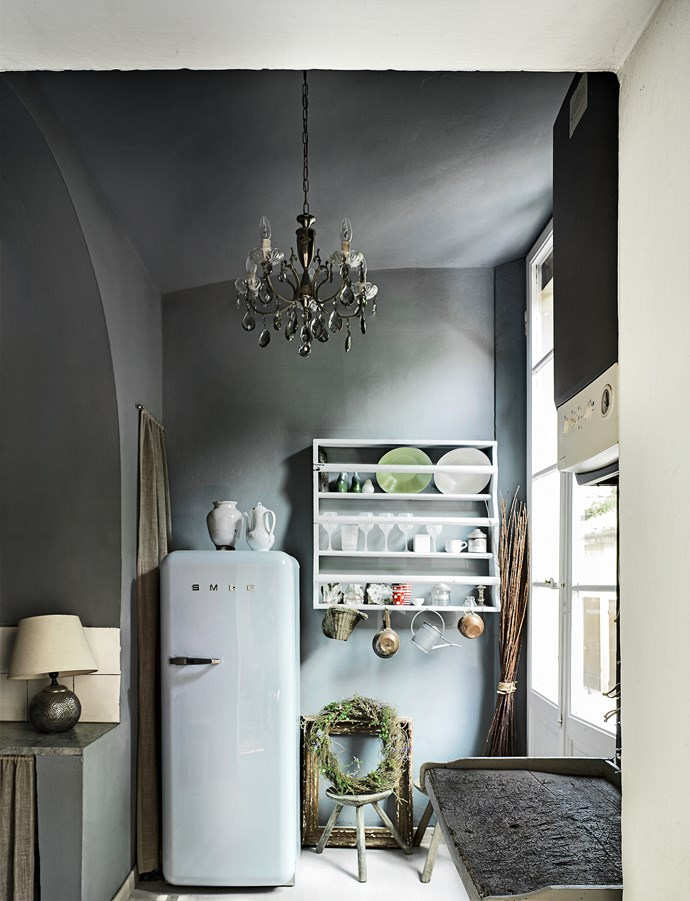 """""""I always have white crockery and love how it stands out against dark grey walls,"""" Benta says. The chandelier adds a polished touch while the tiled splashback and painted dish rack are low-key."""