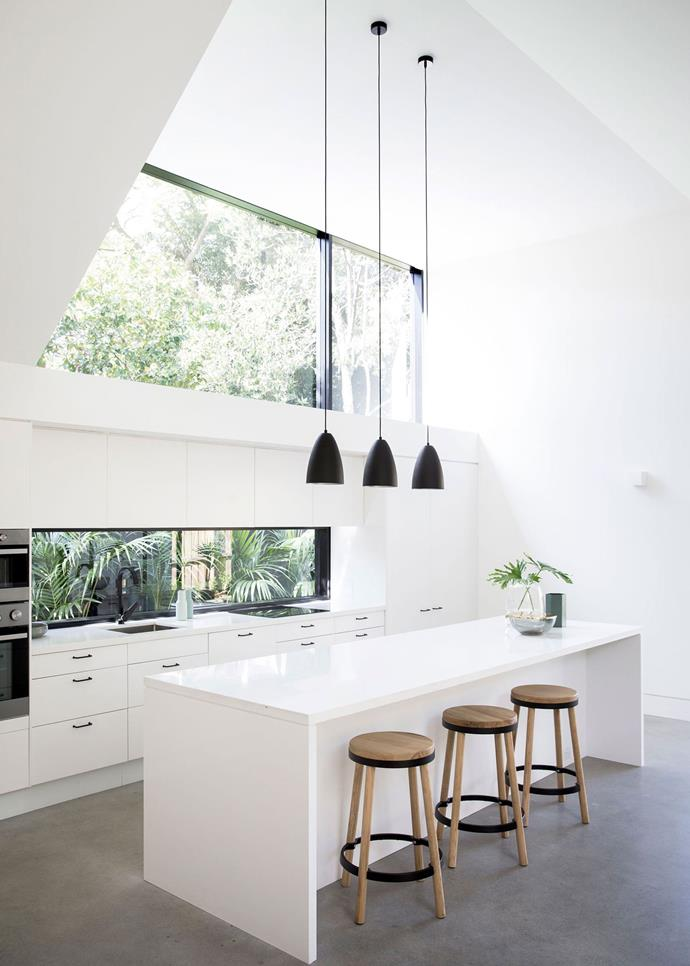 This all-white open kitchen capitalises on the light-filled space perfectly. A glass splashback and large window overhead frame rainforest views which double as a design feature.