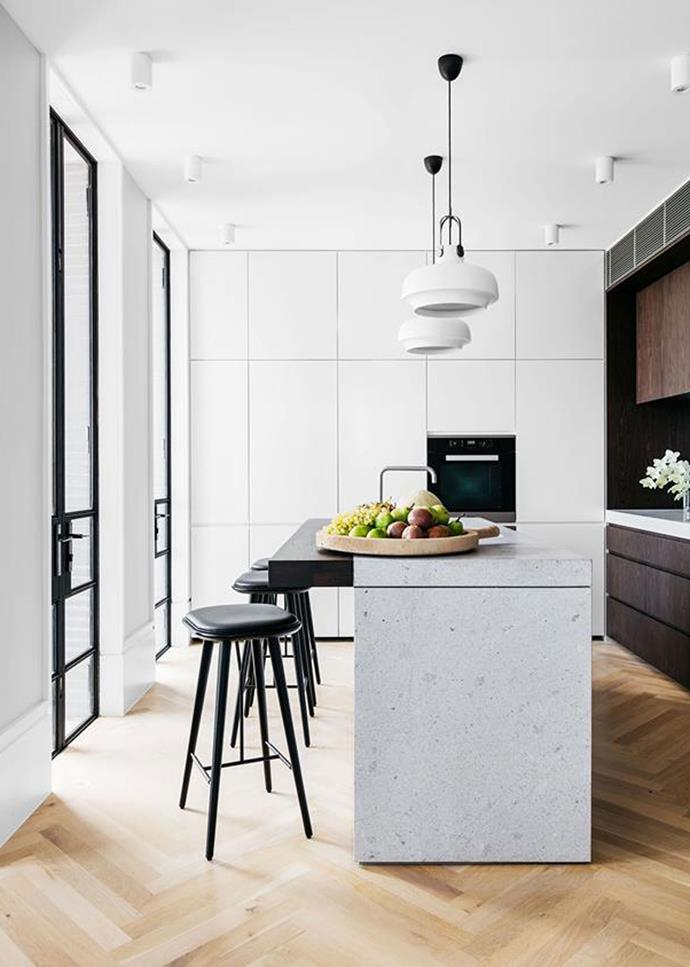 Parquetry floors and statement pendant lights create add character to this modern kitchen that features a range of neutral tones, from stone grey to dark timber.
