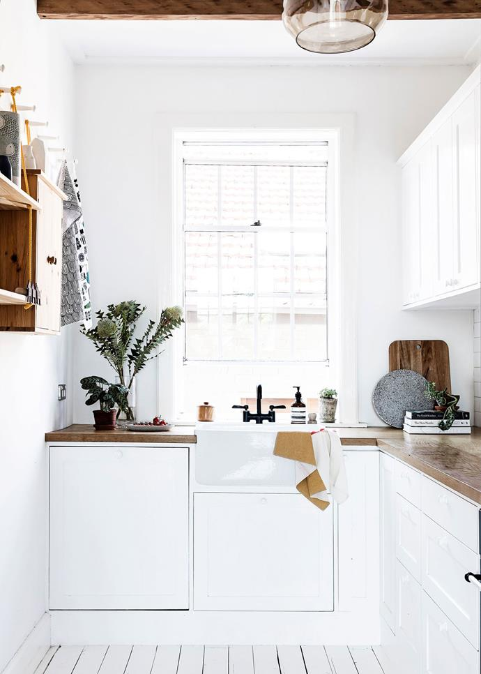 Touches of timber give this all-white kitchen a cosy country feel in this [Scandi-style apartment](http://www.homestolove.com.au/sydney-apartment-gets-swedish-summer-house-makeover-3050).