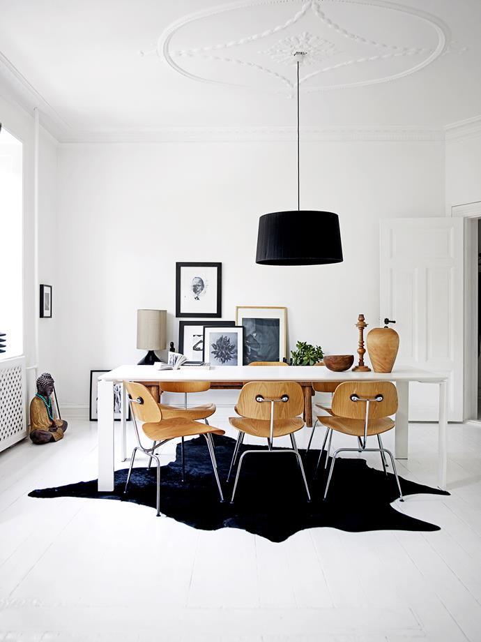 """An organically shaped cowhide rug softens the clean lines of the dining room. A Kartell """"Four"""" dining table is paired with Eames """"DCM"""" dining chairs for an added contrast."""