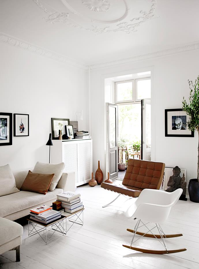 """""""We like to combine items such as wood with white plastic, hide and cotton – like the Arne Jacobsen with a Buddha,"""" Majbritt says. """"Anything can go together as long as it's our taste."""" A small covered balcony, which the family uses all year round, extends out from this part of the home."""
