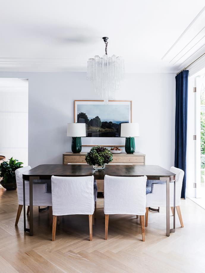 In the dining area, a landscape photograph from Koskela hangs above fluted green glazed table lamps by Natasha Levak. Original 1970s Venini 'Mazzega' blown glass chandelier sourced in Melbourne.