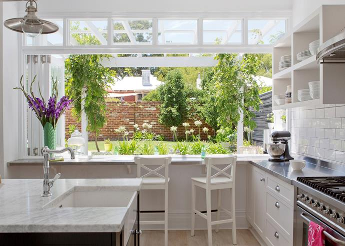This classic country-style kitchen features a bar-style eating space at the window, overlooking the garden. *Photo: Angelita Bonetti*