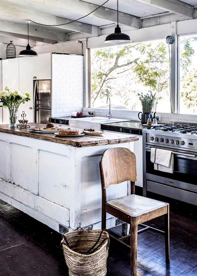 Exposed beams and lighting, raw timber and bare windows give this rural kitchen an authentic, stripped-back feel. *Photo: Felix Forest*