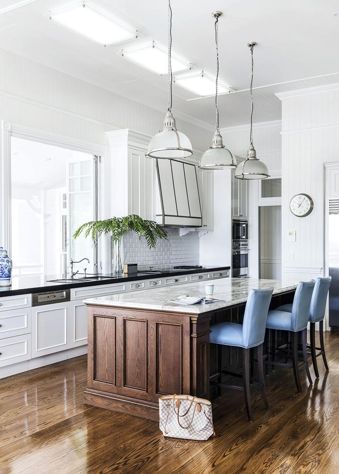 Accents of blue, in bar stools and an ornate vase, provide a gorgeous touch of colour in this provincial country kitchen. *Photo: Maree Homer*