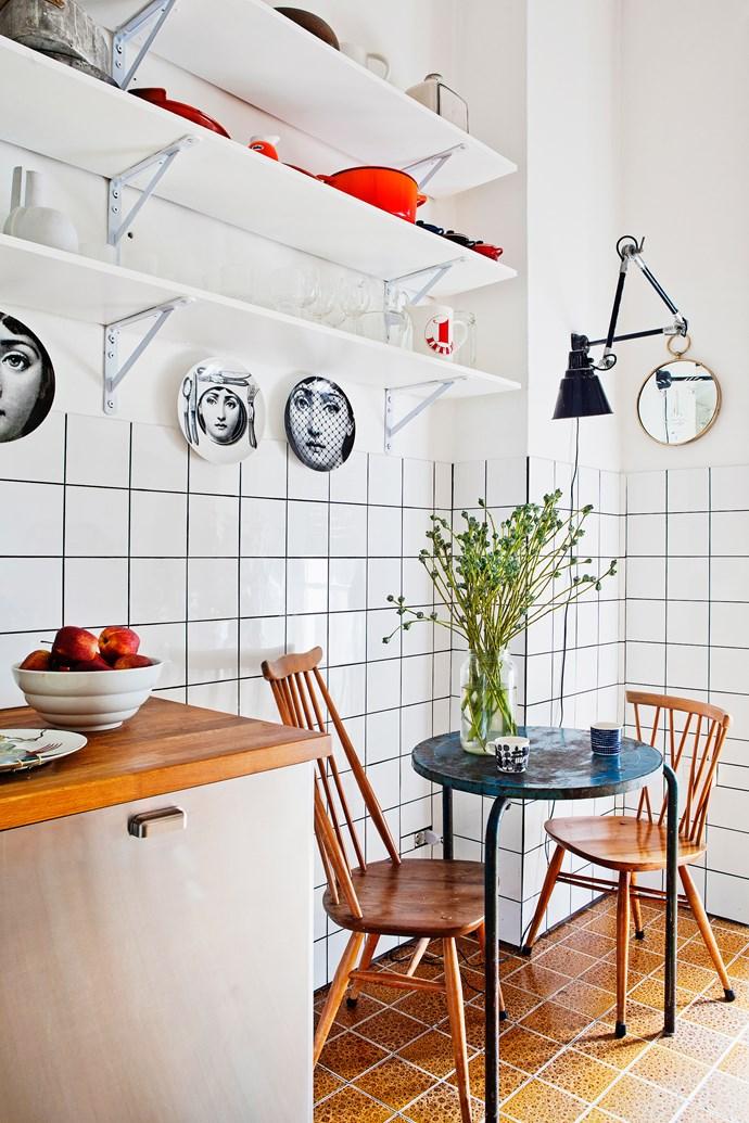 Fornasetti plates adorn the walls in the cute retro kitchen.