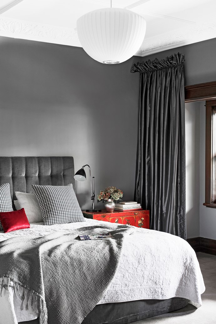 Red accents punch up the restful grey hues of a velvet bedhead and taffeta curtains