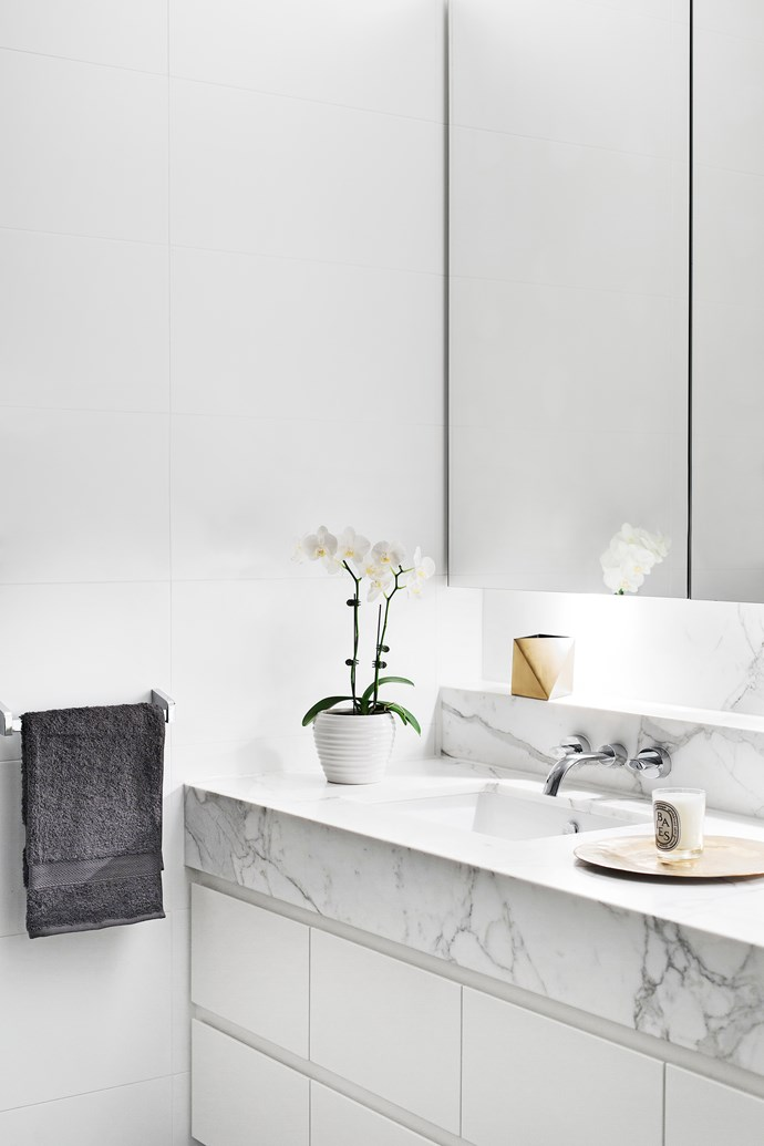 A vanity surface in honed Calacatta marble adds deluxe detailing to this sleek space.